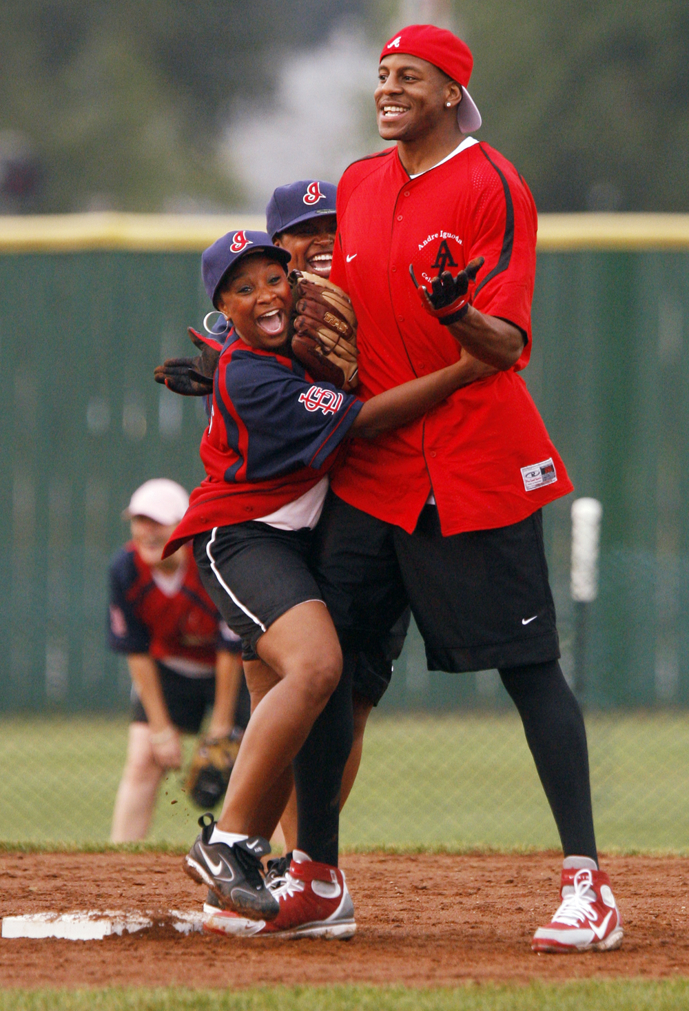 Paris Erwin, left, Nancy Collins and Andre Iguodala argue and laugh after a play at second base Saturday, August 4, 2007 during the Celebrity All-Star Softball Game at Lanphier Park. Iguodala's team of celebrites battled members of the local  media. Ted Schurter/The State Journal-Register
