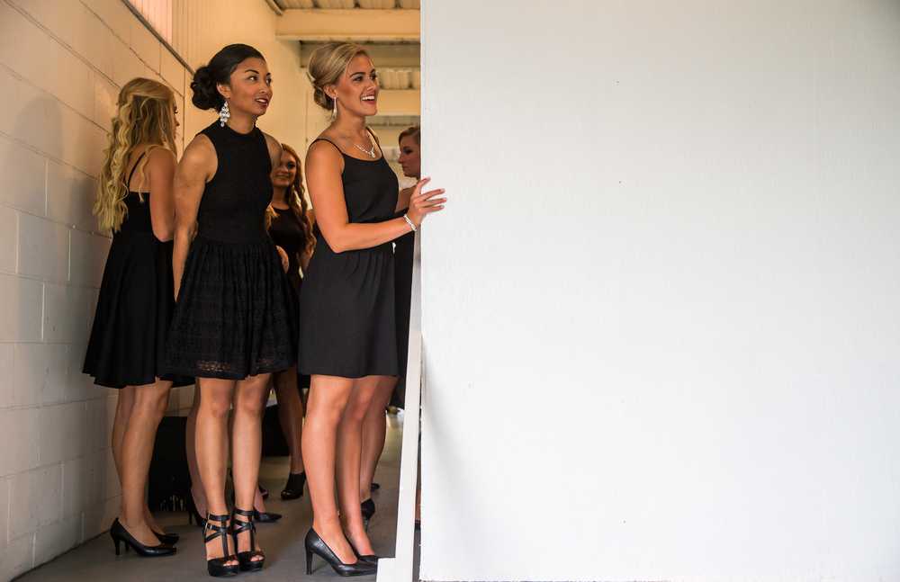 Megan Urbas, center, peaks out from backstage as she looks for family and friends prior to the start of the 57th Annual Sangamon County Fair Queen Pageant at the Sangamon County Fairgrounds, Wednesday, June 17, 2015, in New Berlin, Ill. Justin L. Fowler/The State Journal-Register