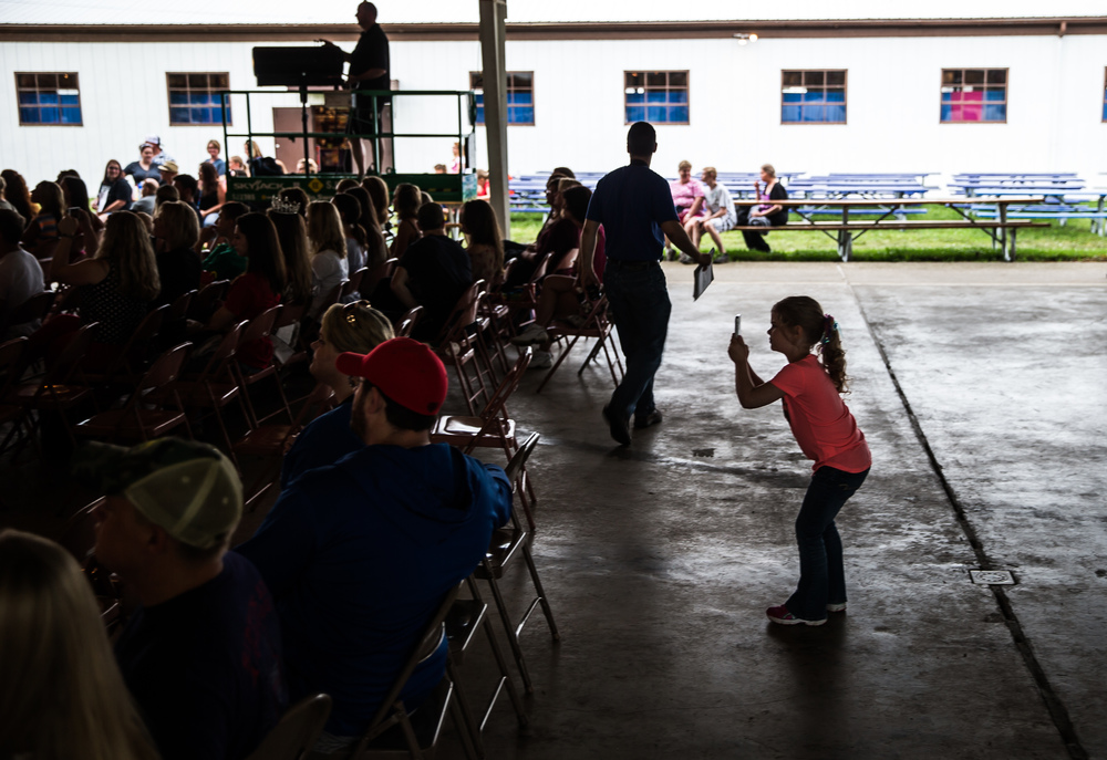 Abby Jones, 4, snaps of photo of the contestants as they walk the runway in the swimsuit competition during the 57th Annual Sangamon County Fair Queen Pageant at the Sangamon County Fairgrounds, Wednesday, June 17, 2015, in New Berlin, Ill. Justin L. Fowler/The State Journal-Register