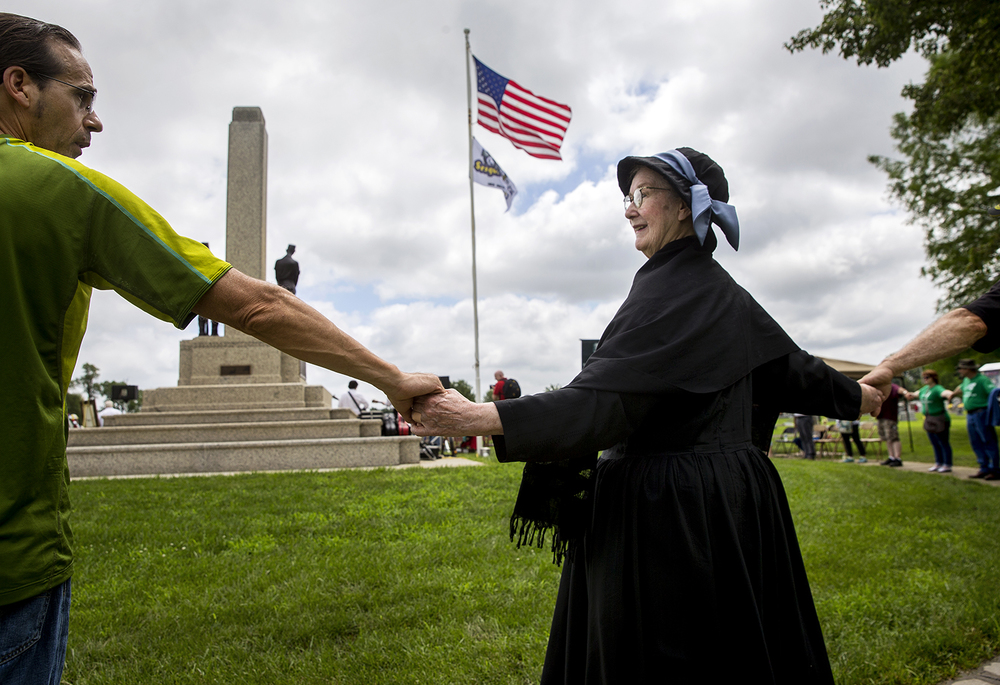 "Margaret Orner of Glen Mills, Pa., portraying labor and community organizer Mary Harris ""Mother"" Jones, grasps hands with Kevin Clarke of Mt. Olive as people circle around the Mother Jones Monument at Union Miners' Cemetery in Mt. Olive during a rededication ceremony Saturday, June 20, 2015. Ted Schurter/The State Journal-Register"