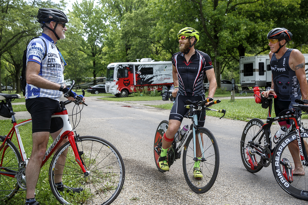 James Lawrence visits with Tom Clark, left, and David Quinn after briefly returning to the  campsite where he started his first bike ride of the day Sunday, June 21, 2015. Lawrence is on a quest to complete 50 Ironman courses in 50 consecutive days through all 50 States. Ted Schurter/The State Journal-Register