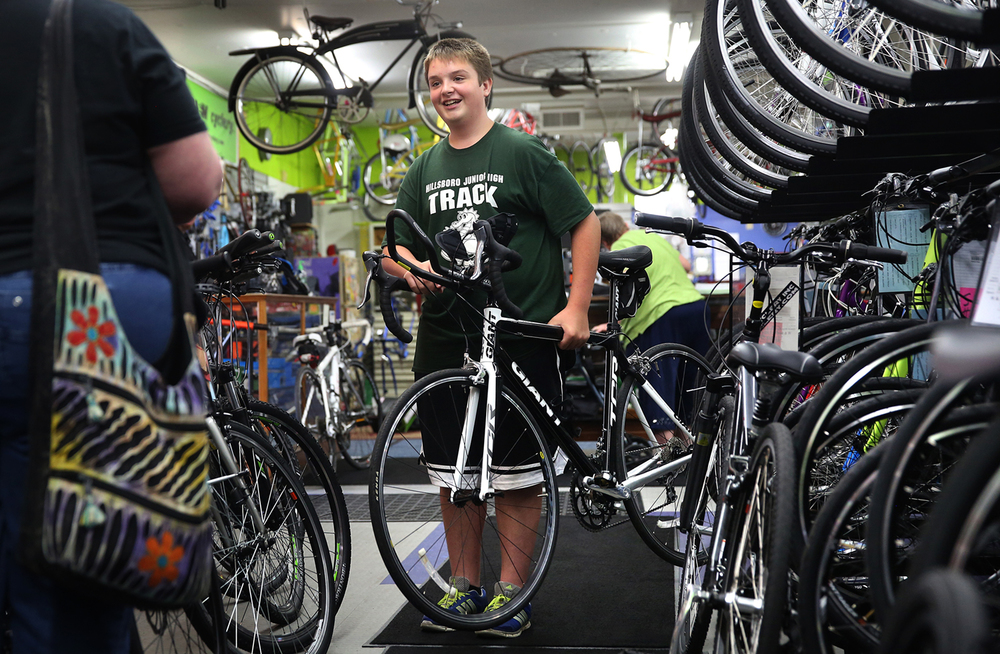 Tommy Stokes smiles while lifting up his new bicycle and realizing how light it is. Hillsboro Junior High School student Tommy Stokes, 14, recently completed the 29-mile annual Roubaix bike race this past April using an old Schwinn bicycle purchased at a rummage sale. On Friday, June 19, 2015, Stokes was presented with a $2,000 carbon-fiber road bike donated by a Montgomery County area doctor in a surprise ceremony at Springfield's R&M Cyclery. David Spencer/The State Journal-Register
