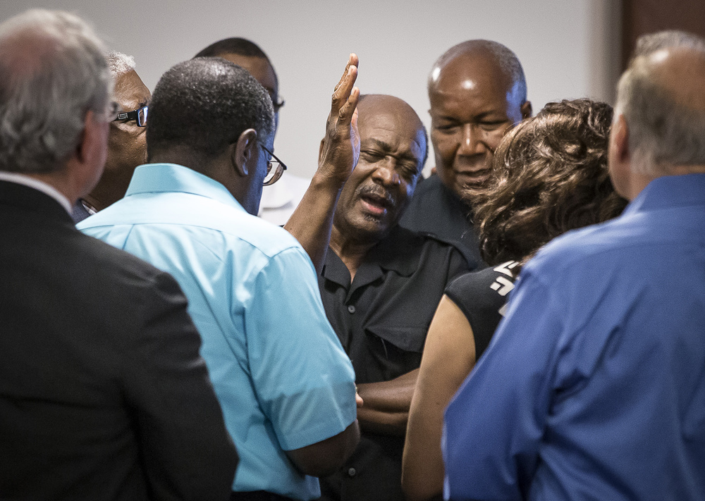 Rev. Charles B. Jackson, center, surrounded by area religious leaders ends a prayer vigil held in response to the mass shooting in Charleston, South Carolina, at St. John's AME Church, 1529 E. Capitol Ave.,, Thursday, June 18, 2015, in Springfield, Ill. Justin L. Fowler/The State Journal-Register