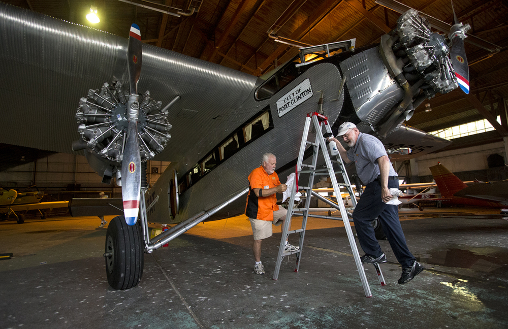 Experimental Aircraft Association members Dan Kerns, left, and John Salz cleaned the windows of a 1928 Ford Tri-Motor 5-AT-B as they waited out rain showers in a hangar at Abraham Lincoln Capital Airport Thursday, June 18, 2015. The plane was available for public rides. Ted Schurter/The State Journal-Register