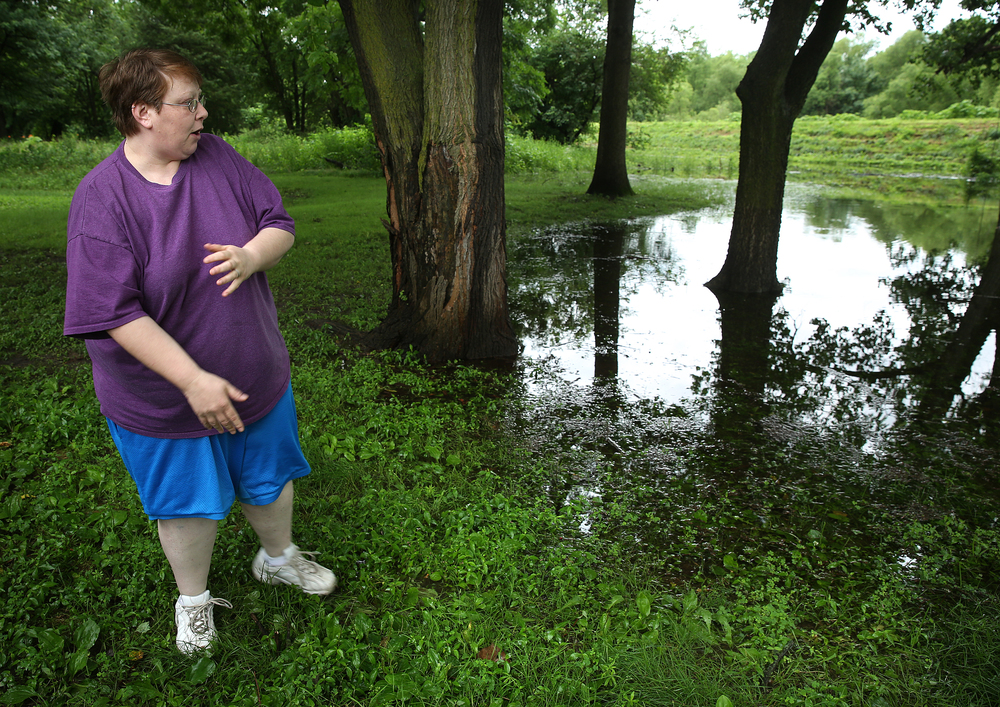 Meredosia resident Heather Baker was keeping a watchful eye on water rising in her backyard in the 400 block of Lake Rd. Wednesday. At far right can be seen the river levee. David Spencer/The State Journal-Register