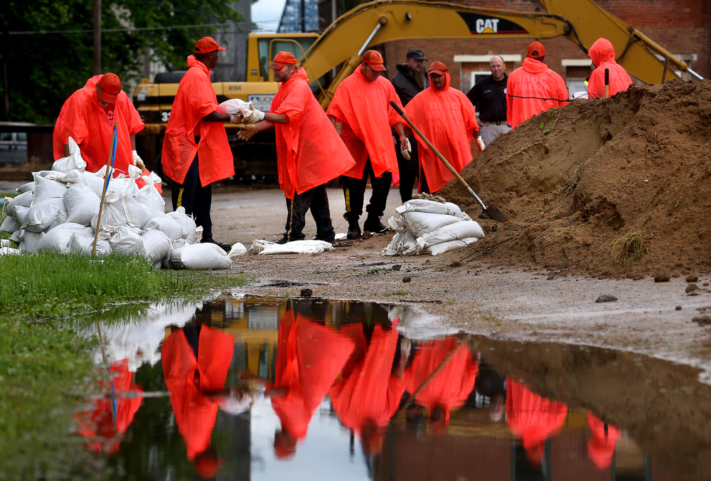 IDOC prisoners form a chain and hand off filled sandbags to the pile at left while being reflected in water that collected in a swale after heavy early morning rains.  David Spencer/The State Journal-Register