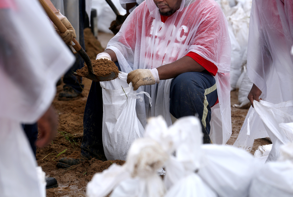 An IDOC prisoner holds a sandbag open while it is filled by a fellow inmate at James Boyd park Wednesday morning. David Spencer/The State Journal-Register