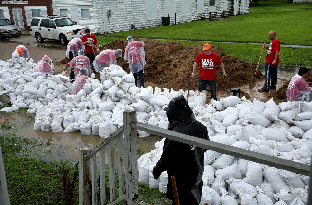 IDOC prisoners fill sandbags with dirt at James Boyd park on Wednesday morning.  David Spencer/The State Journal-Register