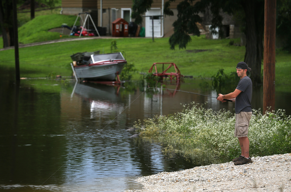 Water can be seen creeping up towards the rear of homes along N. Washington St. as resident Jesse Myers took part of his morning fishing nearby. David Spencer/The State Journal-Register
