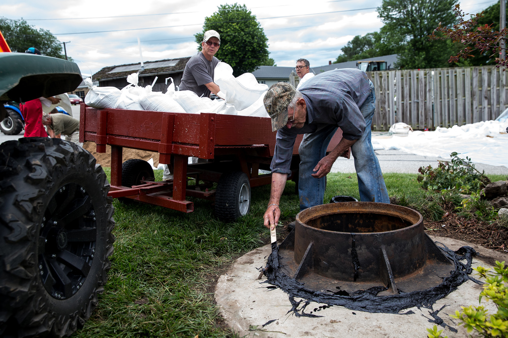 Wesley Hilst, center, uses tar to try and seal the connection of a sewer pipe to try and keep it from leaking out if flood waters overtake it as the Illinois River continues to rise, Thursday, June 25, 2015, in Havana, Ill. Justin L. Fowler/The State Journal-Register