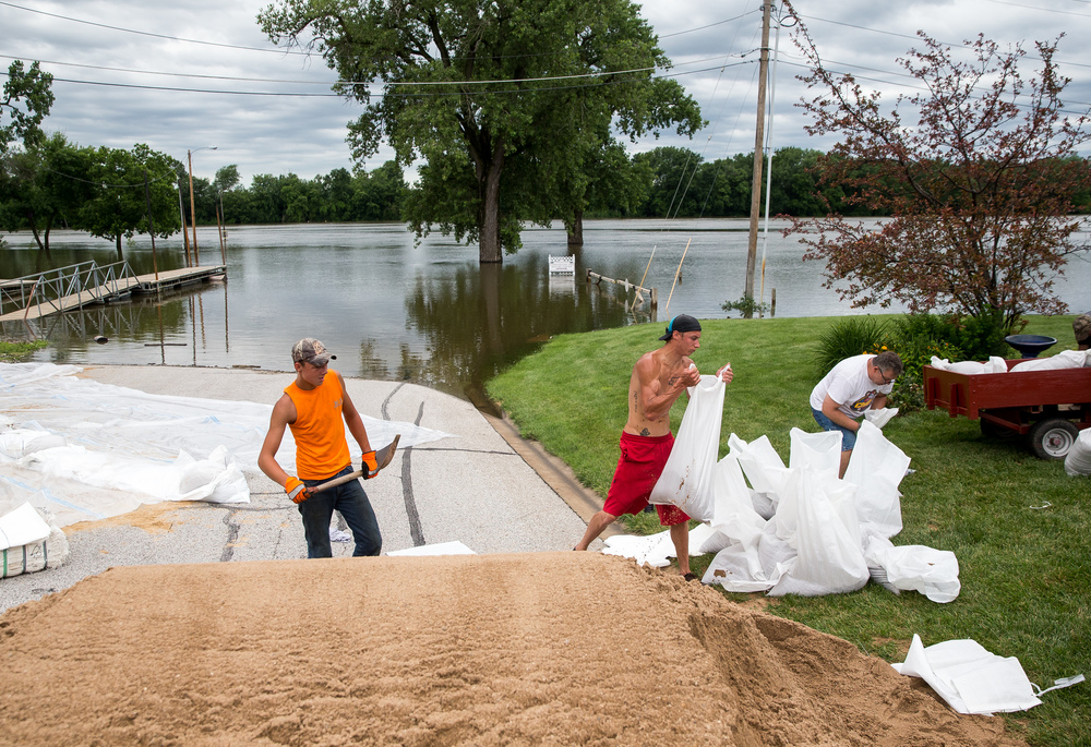 Cody Hilst, 14, left, and Logan McDaniel, right, of C&M Lawn Care, load sandbags to build a wall to protect the property of Wesley Hilst, Cody's grandfather, from flood water as the Illinois River continues to rise, Thursday, June 25, 2015, in Havana, Ill. Justin L. Fowler/The State Journal-Register
