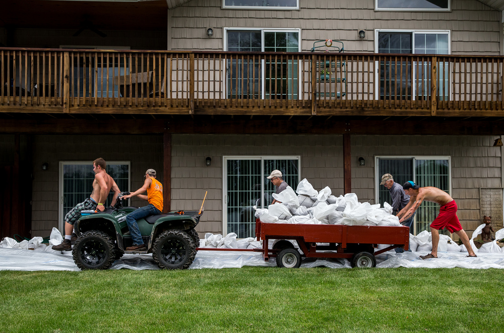 Sandbags are hauled across the property of Wesley Hilst to build a wall to hold back the rising waters of the Illinois River as it overflows its banks, Thursday, June 25, 2015, in Havana, Ill. Justin L. Fowler/The State Journal-Register