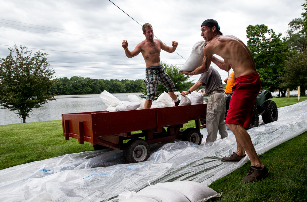 Christopher Hallmark, left, and Logan McDaniel, right,  both of C&M Lawn Care, work at a feverish pace as they throw sandbags down forming a wall to help protect the property of Wesley Hilst from the rising waters of the Illinois River, Thursday, June 25, 2015, in Havana, Ill. Justin L. Fowler/The State Journal-Register