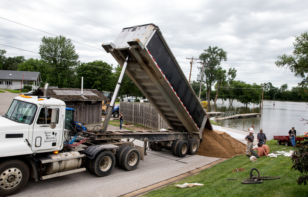 A second load of sand is brought in by Spoon River Blacktop to fills bags for the property of Wesley Hilst in an attempt to hold back the rising water of the Illinois River, Thursday, June 25, 2015, in Havana, Ill. Justin L. Fowler/The State Journal-Register