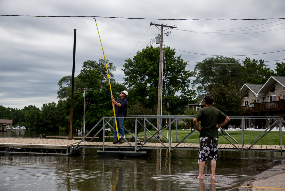 Ameren lineman Greg Curry, of Petersburg, Ill., raises a power line to allow a crew from the Havana Park District to remove the docks from the Illinois River flooding along Riverfront Park, Thursday, June 25, 2015, in Havana, Ill. Justin L. Fowler/The State Journal-Register