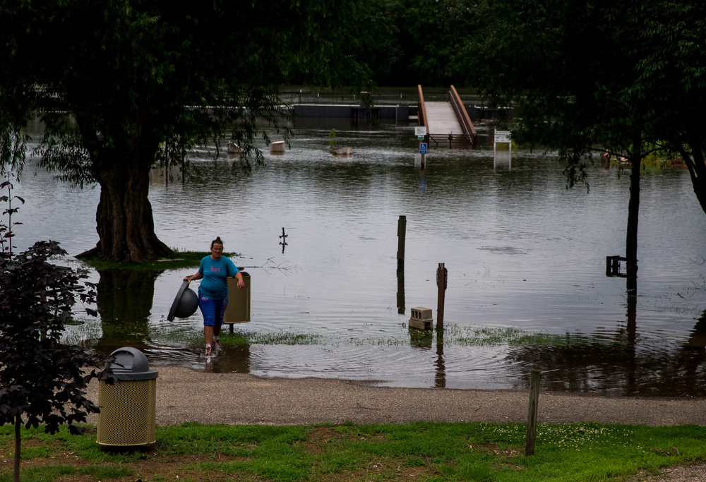 Tonia Gale, of the Havana Park District, removes garbage cans before flood waters overtake them on the Riverfront Park campgrounds as the Illinois River continues to rise, Thursday, June 25, 2015, in Havana, Ill. Justin L. Fowler/The State Journal-Register