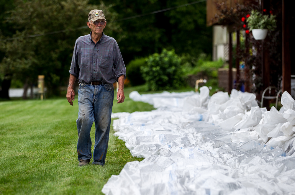 Wesley Hilst surveys a line of plastic as the base for a wall of sandbags to help protect his property from floodwaters as the Illinois River continues to rise, Thursday, June 25, 2015, in Havana, Ill. Justin L. Fowler/The State Journal-Register