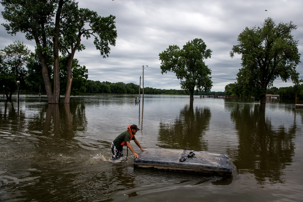 Jason Judd, of the Havana Park District, wades through flood waters as he recovers a float for a dock along the Riverfront Park as the Illinois River continues to rise, Thursday, June 25, 2015, in Havana, Ill. Justin L. Fowler/The State Journal-Register