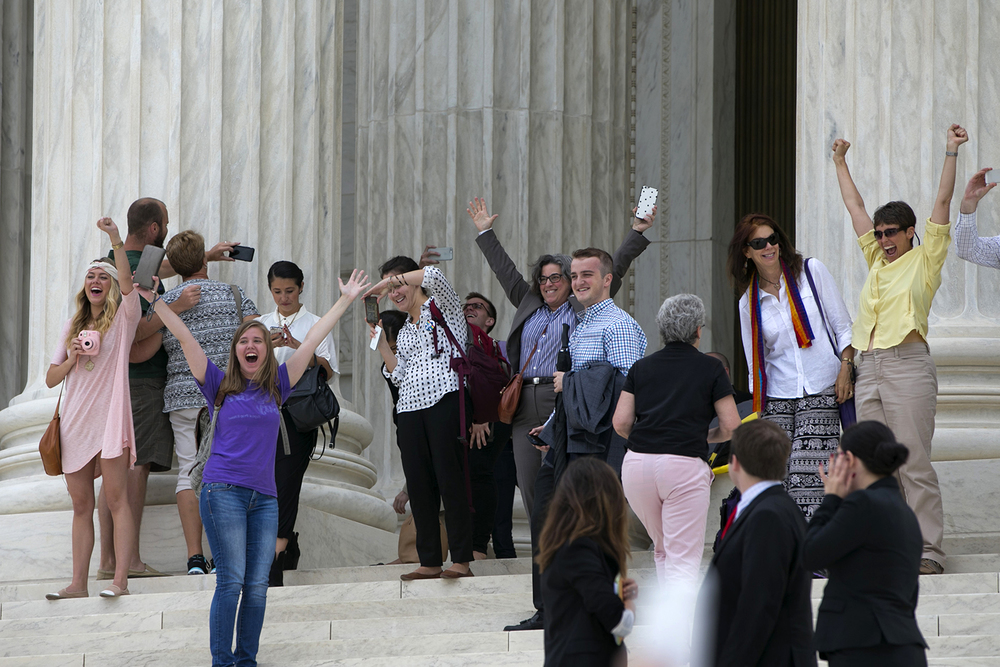 People who were inside the Supreme Court cheer as they walk down the steps of the court in Washington, Friday June 26, 2015,  after the court declared that same-sex couples have a right to marry anywhere in the US. (AP Photo/Jacquelyn Martin)