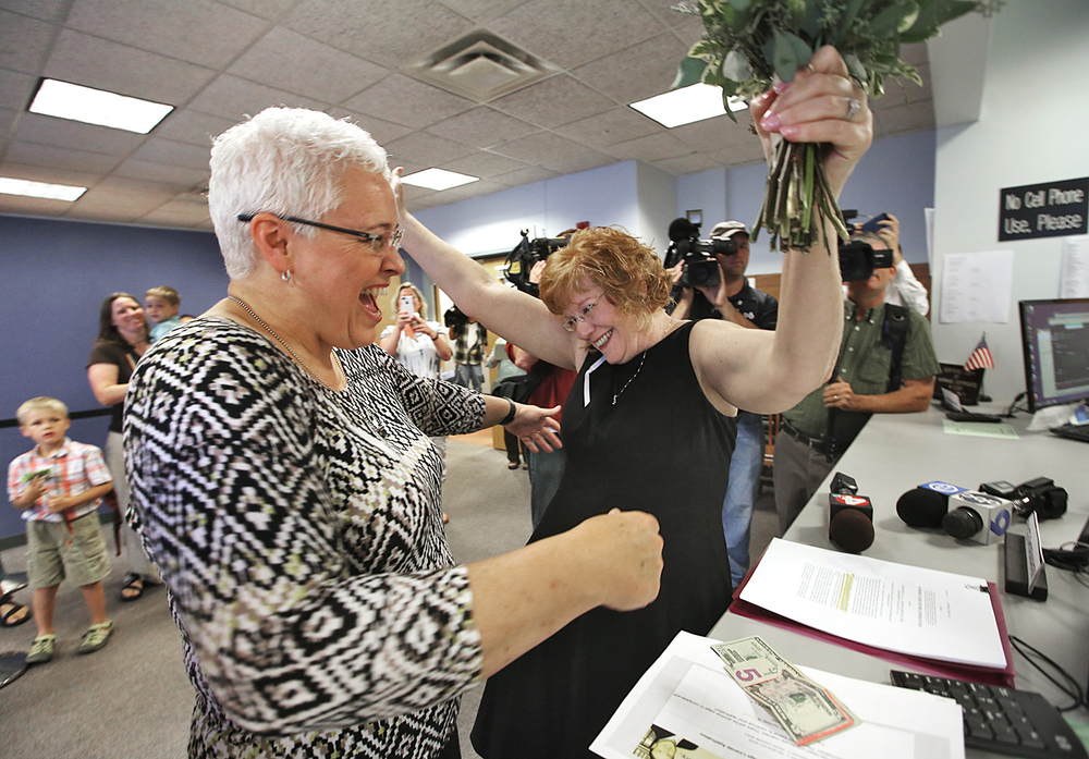 Mindy Ross, left, and Jimmie Beall celebrate at the counter after putting down their money to receive a marriage license in Probate Court on June 26, 2015 in Columbus. The  U.S. Supreme Court's  5-4 ruling means the remaining 14 states, in the South and Midwest, will have to stop enforcing their bans on same-sex marriage. Ohio was one of the 14 states affected by the ruling.  (Chris Russell/The Columbus Dispatch Photo)