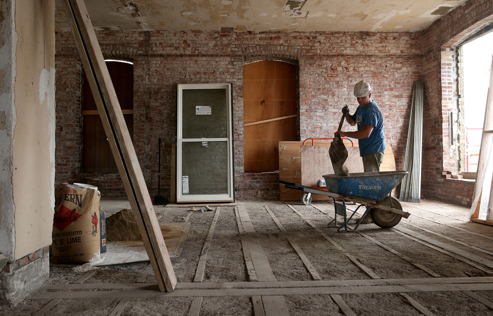 Siciliano, Inc. employee Kyle Harting places debris in a wheelbarrow on the seventh floor of the Booth building. David Spencer/The State Journal-Register