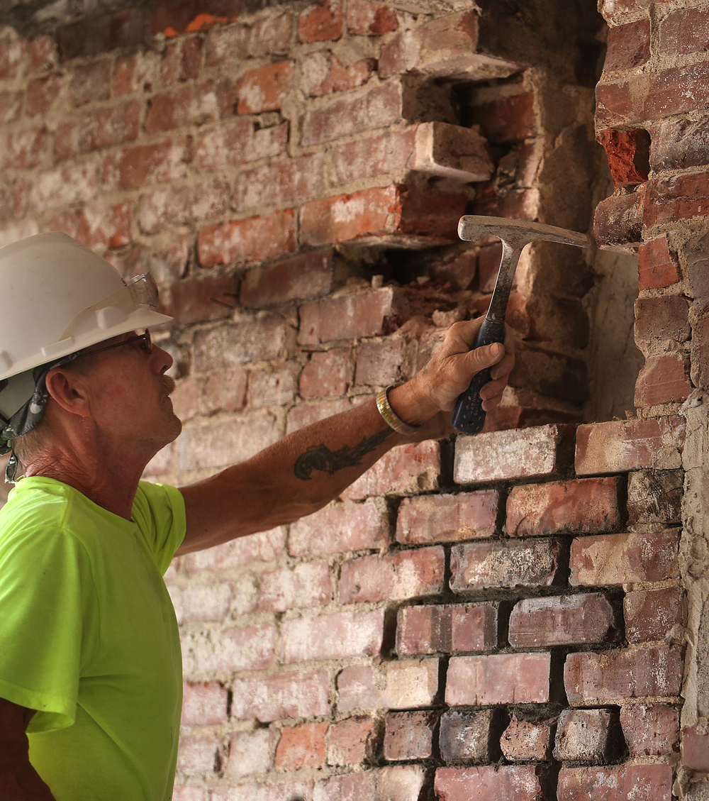 Siciliano, Inc. employee and mason Cliff Foley uses a hammer to chip away mortar from a brick wall while in the process of reconstructing it on the sixth floor of the Booth building. David Spencer/The State Journal-Register
