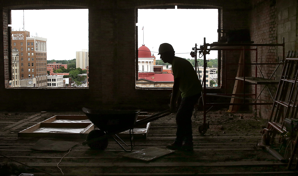 With the dome of the Old State Capitol seen through an open window in the distance, Siciliano Inc. employee Jason Atwood works on the sixth floor of the Booth building. David Spencer/The State Journal-Register