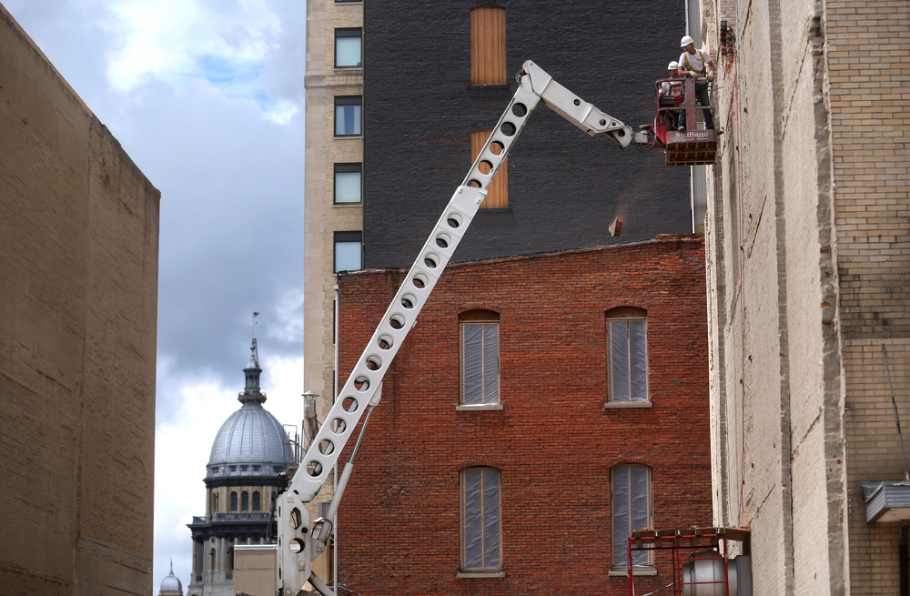 Working form a high-lift, Siciliano workers removed brickwork from an adjoining building (since demolished) that had walled off several floors on the south side of the Ferguson building on May 16, 2015. The Bateman-Kennedy building can be seen at bottom and the Booth building is at rear.David Spencer/The State Journal-Register