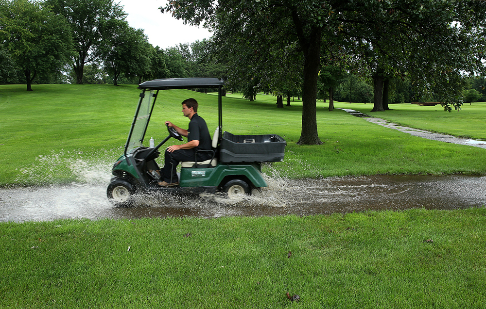 Illini Country Club course superintedent Kyle Sherwood drives a golf cart through water on one of the cart paths at the course in Springfield on Thursday, June 25, 2015. Due to heavy rains this week, the Women's amateur tournament at the course was cancelled. David Spencer/The State Journal-Register