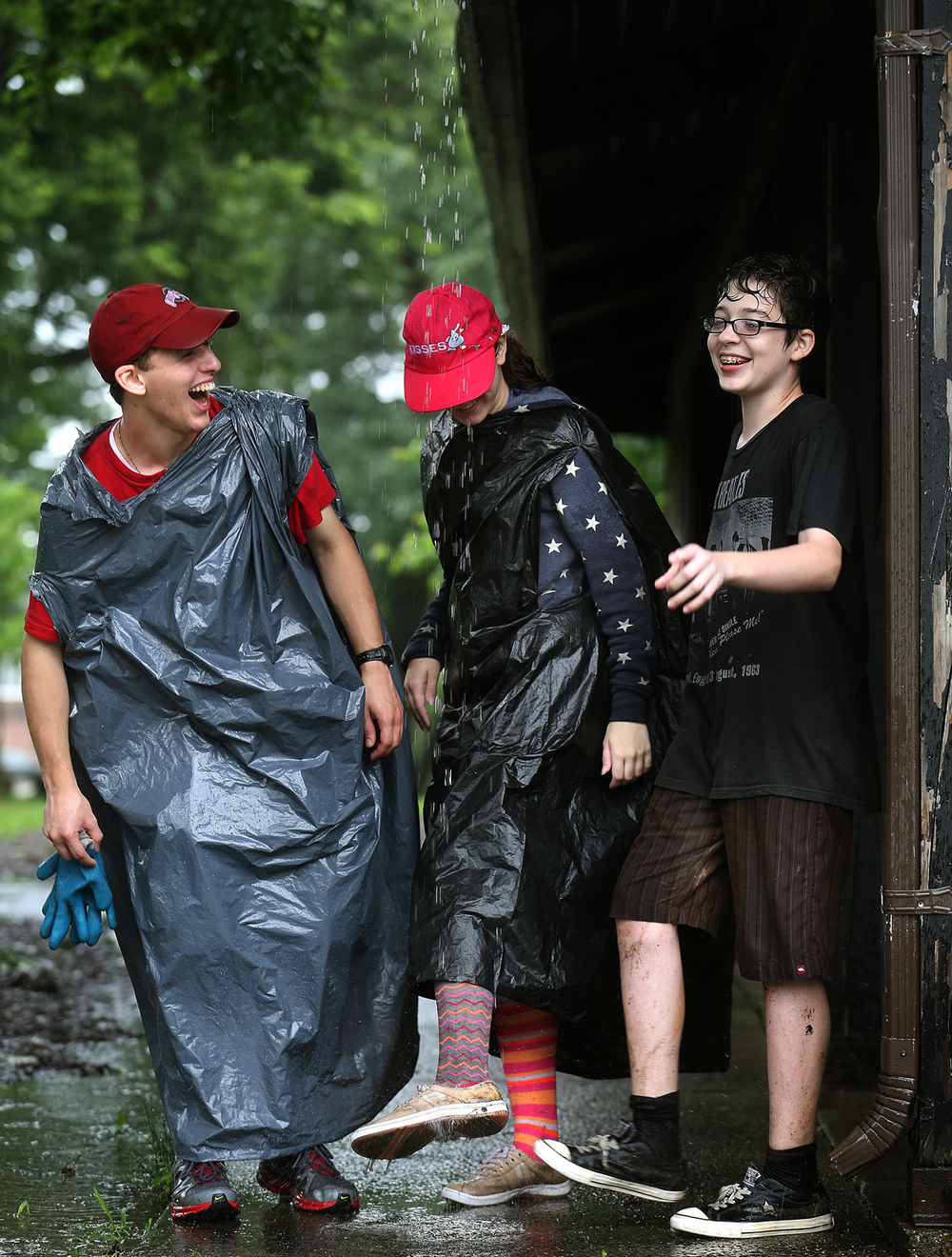 An impromptu shower in the form of rainwater coming off the roof of a pavilion at Springfield's Washington park made for an efficient way of cleaning muddy socks and shoes belonging to members of Alive in You-a Catholic service camp from the state of Virginia visiting Springfield. From left to right are Joe Gillispie, 18, Madi Waldron, 16 and Robert Powers, 14. Part of a group of 14, the campers had been doing cleannup in the children's play area of the park on Friday, June 26, 2015. David Spencer/The State Journal-Register