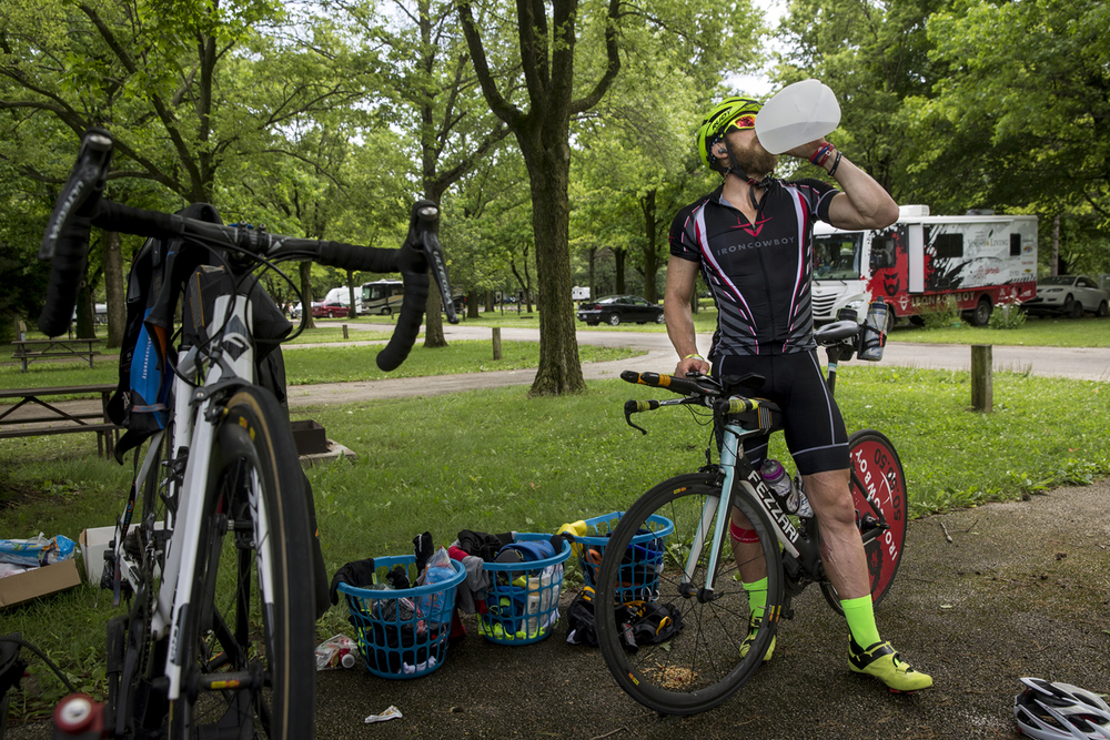 James Lawrence rehydrates after his first bicycling circuit from the New Salem campgrounds into Cass County as he works toward completing his daily Ironman Triathlon miles Sunday, June 21, 2015. Lawrence is on a quest to complete 50 Ironman courses in 50 consecutive days through all 50 States. Ted Schurter/The State Journal-Register