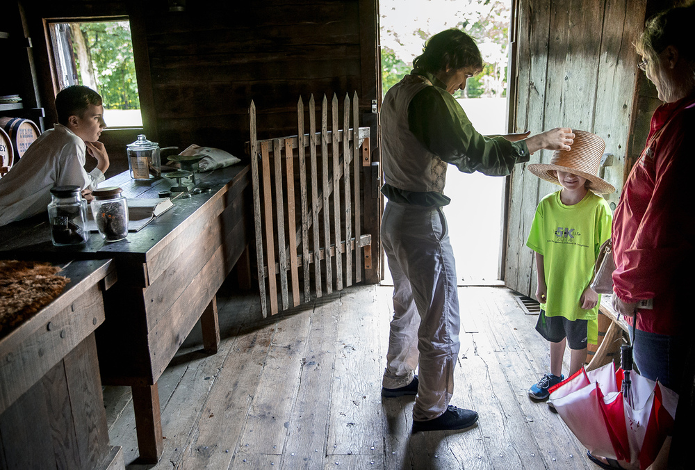 Adam Enz, center, an interpreter intern from Illinois College majoring in communications, lets Carter Caldwell, 7, right, visiting from Oklahoma, try on a straw hat inside the first Berry-Lincoln Store at Lincoln's New Salem State Historic Site, Wednesday, June 24, 2015, in Petersburg, Ill. Enz was mentoring Augie Antonacci, 13, left, how how to to interact with visitors and share Lincoln's story as a part of the Pioneer Life Summer Day Camp. Justin L. Fowler/The State Journal-Register
