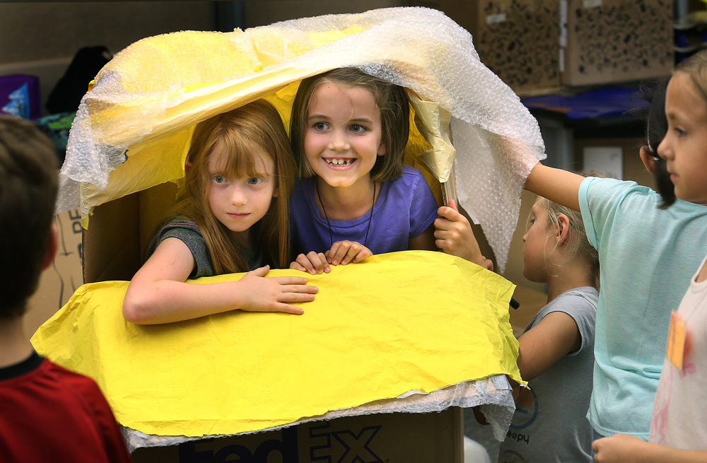 One team-building exercise Monday was students collaborating to build different types of shields from cardboard boxes used for protection in an outdoor water-balloon fight. Calling themselves the Electric Cheetahs, one shield seen here was a protective chamber covered by bubble-wrap. Standing inside are campers Elise Miller at left and Katherine Minch. Camp Invention, a weeklong day camp for 100 students in first through sixth grades kicked off on Monday, June 22, 2015 at the University of Illinois Springfield. The camp focuses on innovation and creativity while building self-esteem, teamwork, persistence and goal-setting skills. With the working theme of Illuminate, teams of campers build inventions from scratch over the course of the week through idea stage to execution, with a formal presentation of their finished inventions held on Friday. David Spencer/The State Journal-Register
