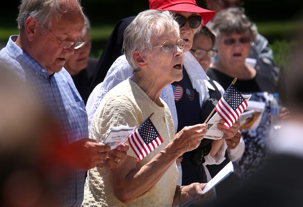 Springfield resident Lois Jirgal at center sings God Bless America along with others during the rally Tuesday afternoon. A prayer rally lead by Bishop Thomas John Paprocki was held in front of the Illinois State Capitol building in 
