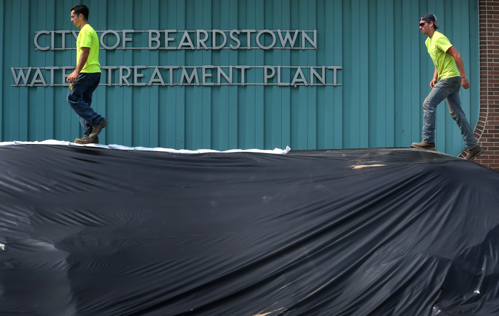 Two Department of Public Works employees walk atop a newly constructed 8' wall of sand surrounding the Beardstown Water Treatment Plant on Wednesday morning. David Spencer/The State Journal-Register
