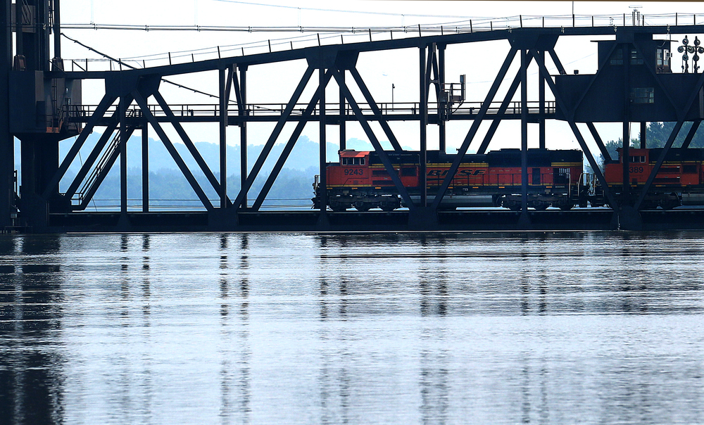 The high water level on the Illinois River was lapping at the very base of the BNSF railroad bridge Wednesday morning as a locomotive pulling cars slowly makes its way over. David Spencer/The State Journal-Register
