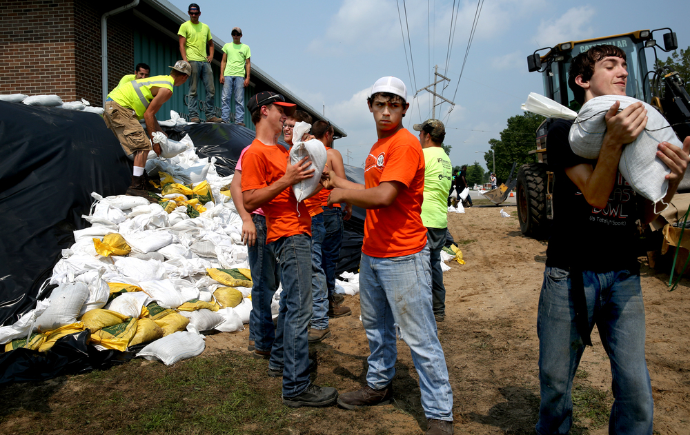 Beardstown Public Works employees form a line and pass off sandbags towards securing an 8' wall of sand forming a wall around the Beardstown Water Treatment Plant on Wednesday morning. David Spencer/The State Journal-Register