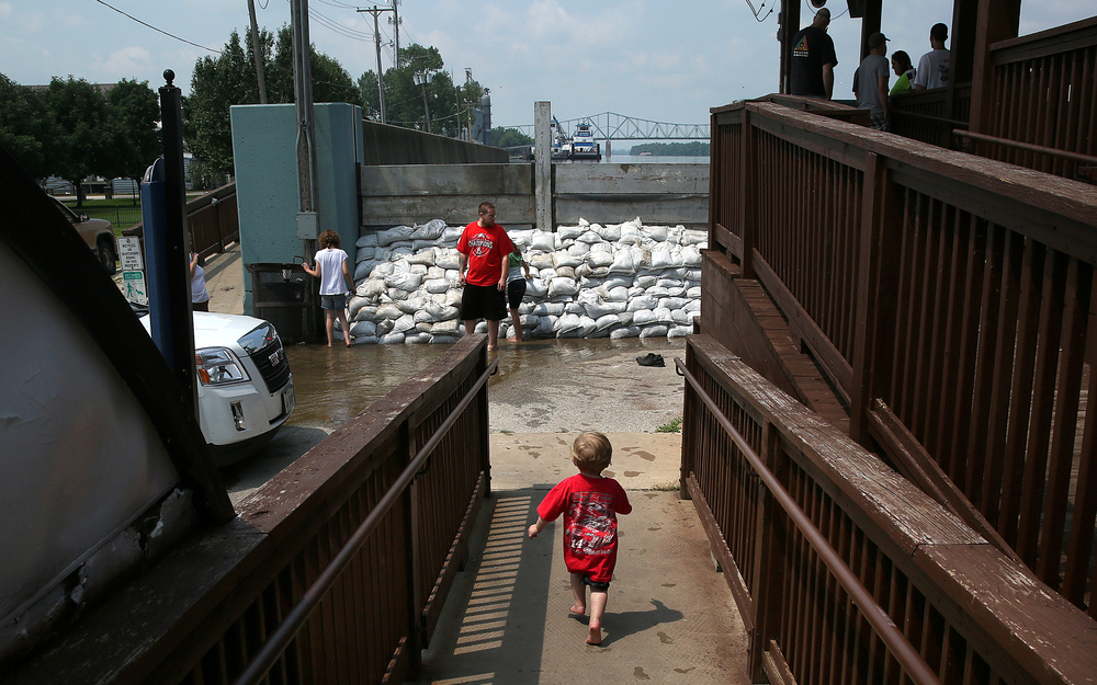 Adyen Green of Beardstown runs towards a small wall of sandbags set up near the base of the Beardstown Overlook on Wednesday morning. Water leaking through the sandbags made a small pool that was fun to run through for Adyen and his siblings Alexandra Dunn and Kayda Nava. David Spencer/The State Journal-Register
