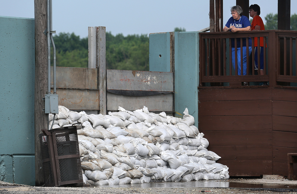After running a few errands Wednesday morning, Arenzville resident Teresa Fisher walked over to the Beardstown Overlook to check out the high river and to take in a small wall of sandbags seen at bottom of frame that were leaking, although Fisher said it was a common occurrence. David Spencer/The State Journal-Register