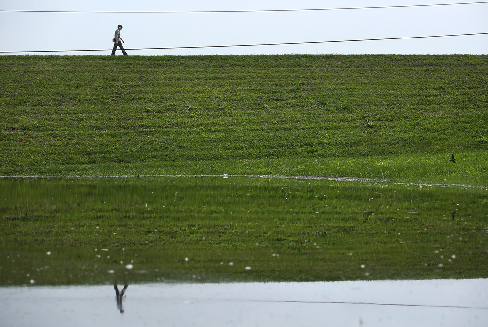 A walker atop the Beardstown Marina levee is seen reflected in floodwaters from the vantage point of the now closed Schmoldt Memorial Park in Beardstown. David Spencer/The State Journal-Register