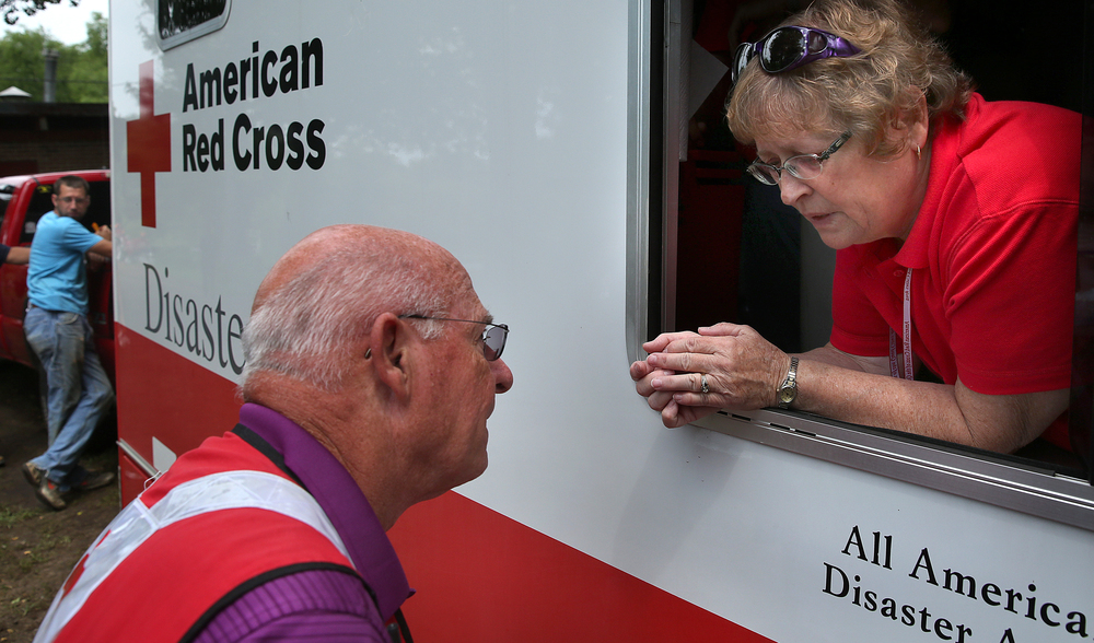 Red Cross volunteer Sue Anderson of Davenport, Iowa speaks with a fellow volunteer during a lull in serving lunch while parked at the end of Gaskill St. Thursday. David Spencer/The State Journal-Register