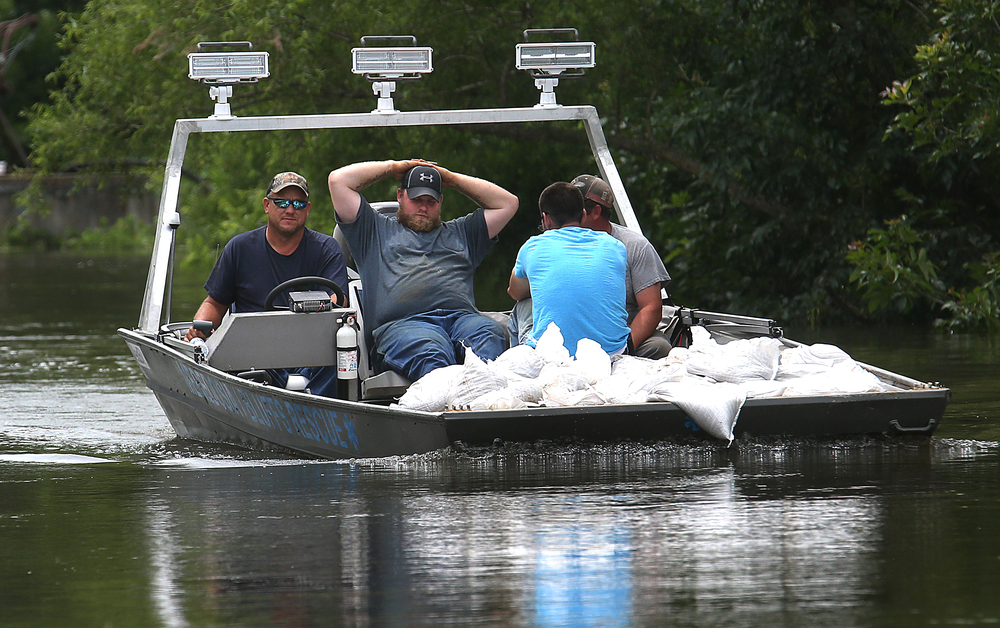 Hundreds of sandbags are transported by members of Meredosia/Bluffs River Rescue to the levee that backs up to Lake Rd. on the north side of Meredosia Thursday. David Spencer/The State Journal-Register