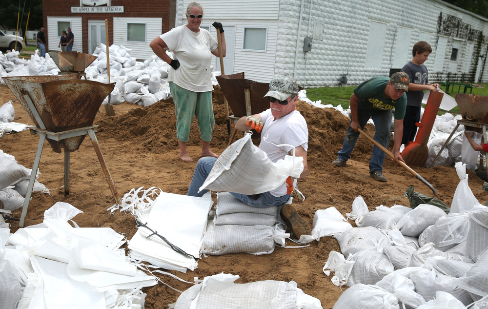 Larry Johnson of Meredosia heaves another filled sandbag on a pile at James Boyd Park. Johnson was filling sandbags with wife Bonnie Johnson who stands in background. David Spencer/The State Journal-Register