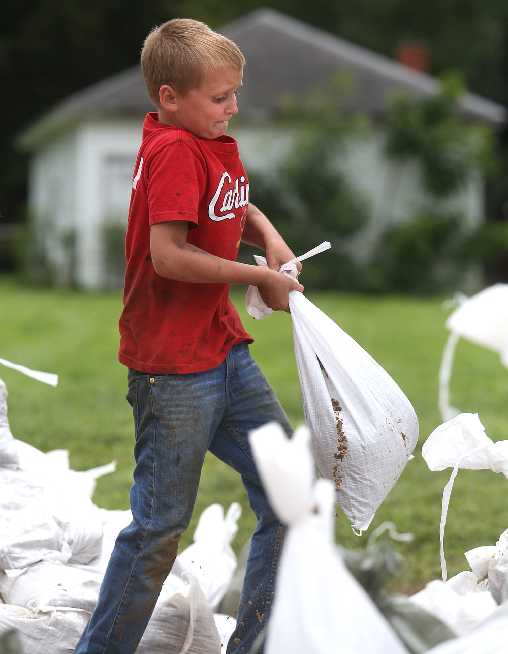 Eight-year-old Owen Luckett was getting a workout while filling sandbags at James Boyd Park on Thursday. Luckett, who had been filling bags for about an hour at the time this photo was taken said he was enjoying the task. Also helping him was his older brother Gregory Luckett and friend Wesley Gooding. David Spencer/The State Journal-Register