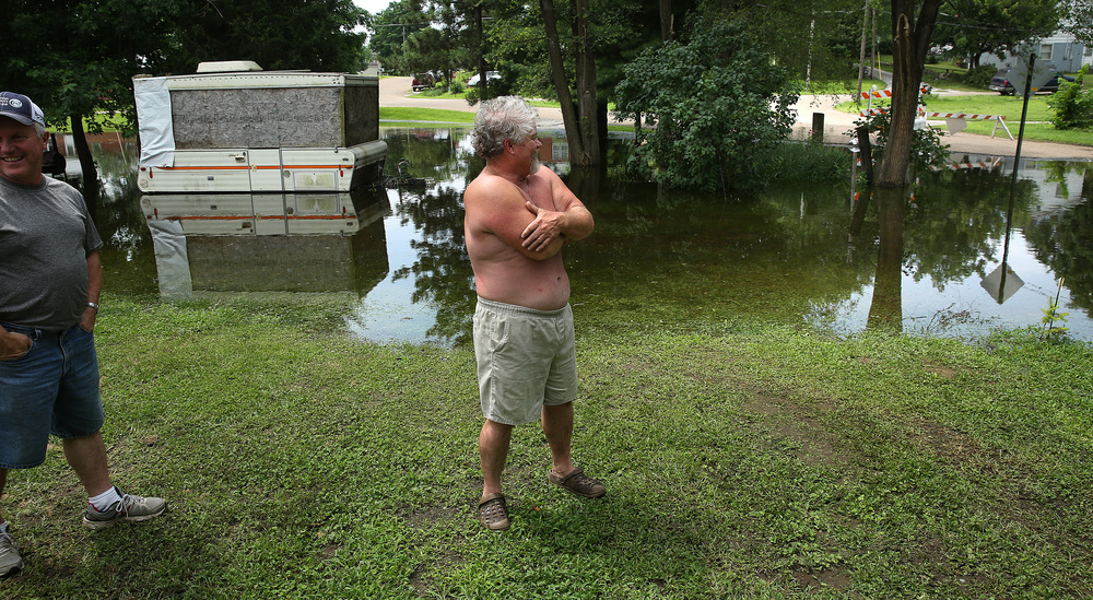 Poco Casa Drive resident Mike Stinson at center surveys his flooded backyard on Thursday. Stinson, a long-time Meredosia resident said it was the worst flooding he has seen in his neighborhood. David Spencer/The State Journal-Register