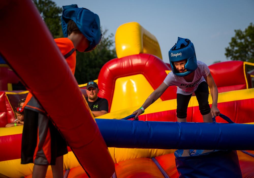 Katie Sowers, 9, goes low to try and knock her brother, John Sowers, 6, off the pedestals during a game of inflatable jousting during the Riverton Fire Crackin' Festival at the Knights of Columbus Marian Council 3914, Friday, July 3, 2015, in Riverton, Ill. Justin L. Fowler/The State Journal-Register
