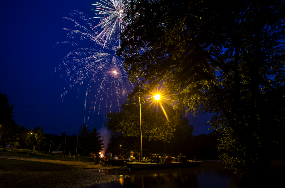 Fireworks explode over the Sangamon River as boats parked on its flooded over banks during the Riverton Fire Crackin� Festival at the Knights of Columbus Marian Council 3914, Friday, July 3, 2015, in Riverton, Ill. Justin L. Fowler/The State Journal-Register