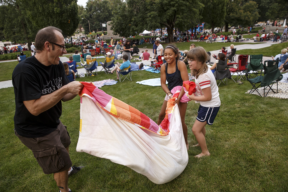 Bob Ayers helps Olivia Antonacci and his niece Trinity Ayers swing Megan Antonacci in a blanket as they wait on the Capitol lawn for the fireworks Saturday, July 4, 2015.  Ted Schurter/The State Journal-Register