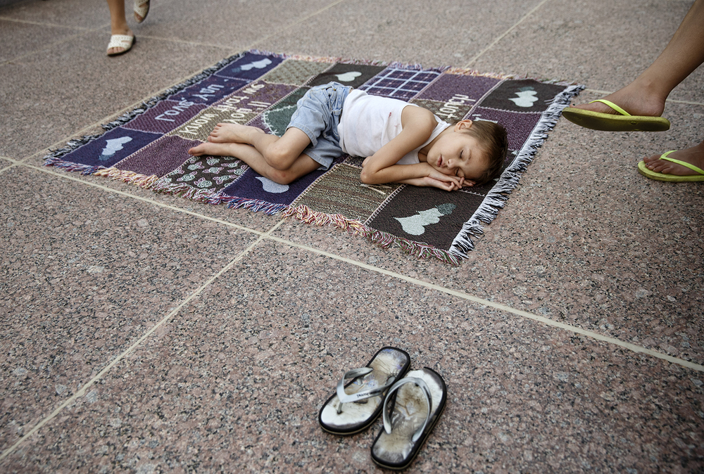 Nine-year-old Anthony Presnell fell asleep on a rug in front of the Capitol while waiting for fireworks Saturday, July 4, 2015. Ted Schurter/The State Journal-Register