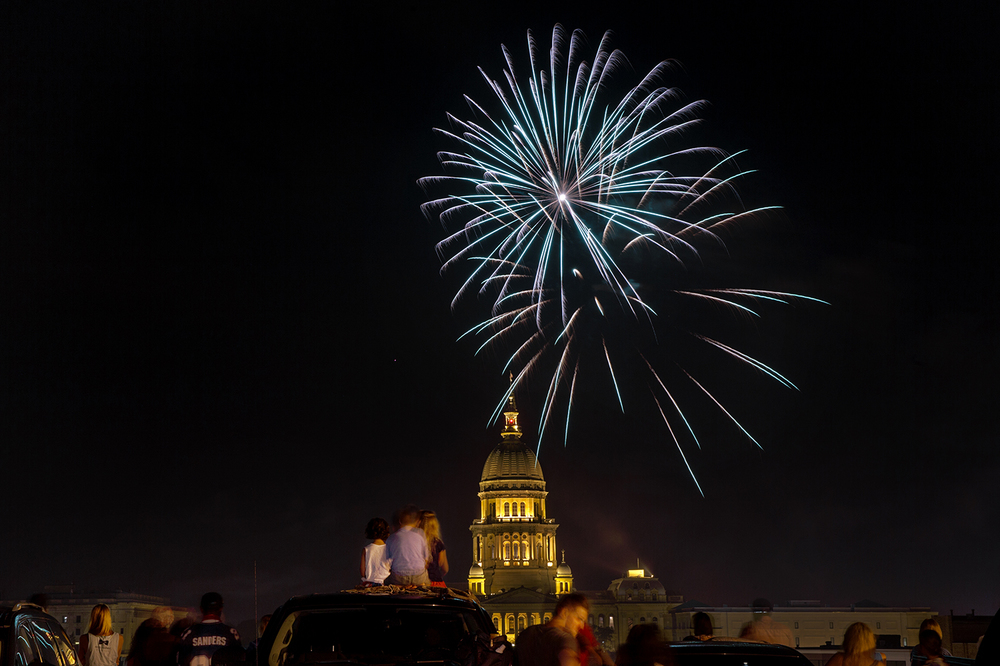 A line of spectators line up at the edge of the top floor of a downtown parking garage to watch the fireworks explode above the Capitol dome during the Capital City Celebration Saturday, July 4, 2015.  Ted Schurter/The State Journal-Register